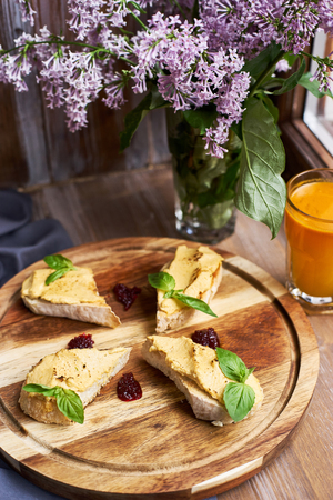 Crispy chiabatta toasts with chicken pate and onion confiture served on round wooden board on table decorated with lilac flowers. Glass of sea buckthorn berries juice. Heathy food.