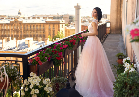 Tender outdoor full length portrait of young beautiful elegant woman with brunette hair and hairstyle standing and posing in long fluffy pink dress at summer terrace on sunny summer day