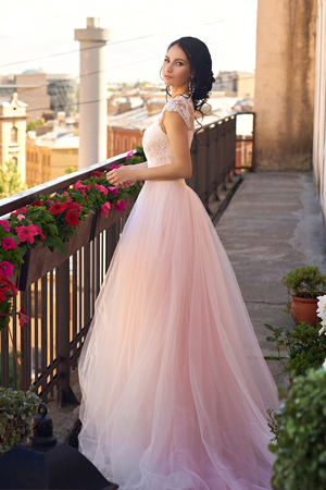 long: Tender outdoor full length portrait of young beautiful elegant woman with brunette hair and hairstyle standing and posing in long fluffy pink dress at summer terrace on sunny summer day