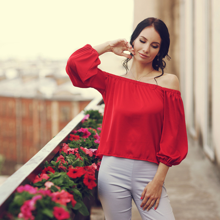 Beautiful syulish girl outdoor portrait. Summer style. Fashionable woman wearing red blouse and bright trousers standing at terrace near rails with flowers in blossom.