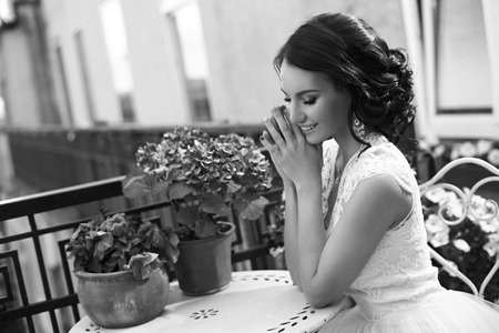 long: Outdoor portrait of young beautiful pretty caucasian brunette bride posing in white fluffy dress. Attractive girl sitting at terrace on summer sunny day. Stock Photo