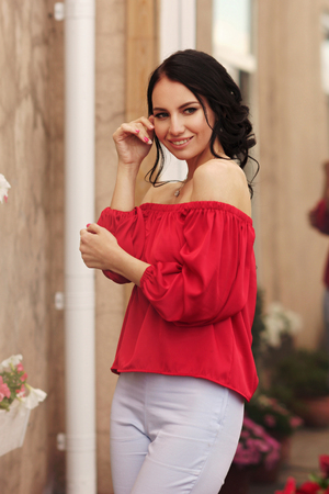 Young beautiful caucasian brunette woman with hairstyle posing at summer terrace with with on city buildings. Attractive girl in trousers and red blouse.