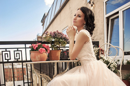 long: Young pretty stylish bride in fluffy white dress sitting at summer terrace. Beautiful young woman with hairstyle and make posing on a sunny day with blue sky