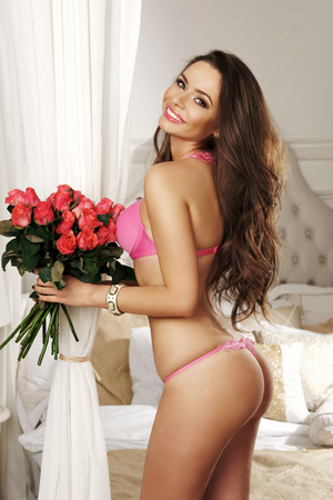 Smiling brunette model with long wavy hair dressed in pink lace bra and thong panties standing half-turned against large luxury bed on background and holding bouquet of rose flowers in her hands. Stock Photo