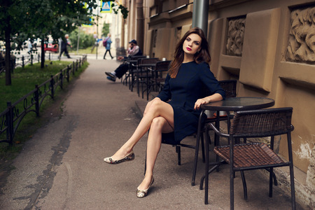 Lovely young brunette woman, wearing black skater dress with shortened sleeves, sitting with her legs crossed in chair at table of outdoor cafe. Gorgeous female model posing beside antique building. 版權商用圖片