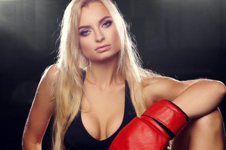 repose: Half portrait of young blonde woman with long hair, dressed in black sports bra, pink shorts and red boxing gloves, looking to right side. Lovely female boxer posing. Concept of strength and power. Stock Photo