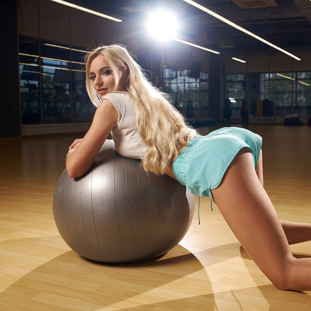 Seductive blonde woman, dressed in fitness clothing, standing half-turned on her knees on wooden floor and leaning on large gray exercise ball. Attractive fitness model posing in sexy position Standard-Bild