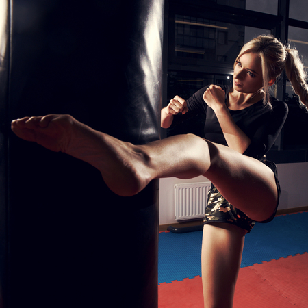 Gorgeous female fighter with blonde hair pulled back in long braid, dressed in black crop top and camouflage shorts, hitting punching bag with her leg. Attractive young woman training in sports club. Stockfoto