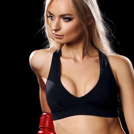 Half portrait of young blonde woman with long hair, dressed in black sports bra, pink shorts and red boxing gloves, looking to right side. Lovely female boxer posing. Concept of strength and power. Archivio Fotografico