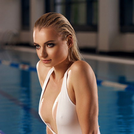 Seductive blonde woman with long wet hair dressed in white swimsuit with low-cut neckline standing in swimming pool and leaning on edge with her hands. Sexy female model emerging from blue water. Stockfoto