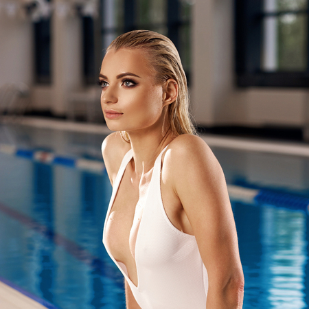 Seductive blonde woman with long wet hair dressed in white swimsuit with low-cut neckline standing in swimming pool and leaning on edge with her hands. Sexy female model emerging from blue water. Standard-Bild