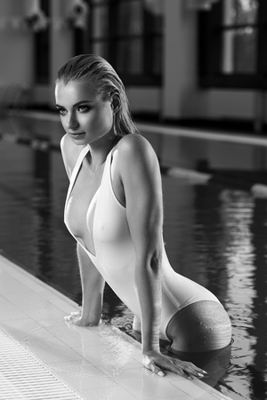 Seductive blonde woman with long wet hair dressed in white swimsuit with low-cut neckline standing in swimming pool and leaning on edge with her hands. Sexy female model emerging from blue water. Stock Photo