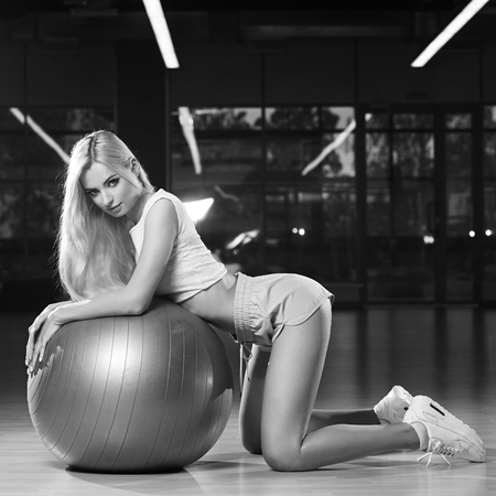 Pretty woman with long blonde hair, dressed in sports clothing, kneeling down on wooden floor and leaning on gray swiss ball with her forearms. Attractive female fitness model posing in spacious gym.