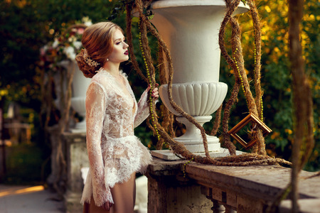 Elegant female model wearing maxi dress and white lace jacket with long sleeves posing on summer terrace beside classical stone balustrade and large flower vases against green foliage on background. Standard-Bild