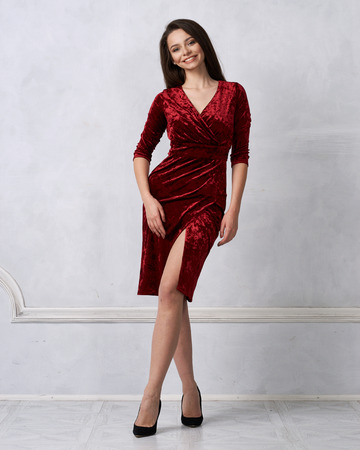 Gorgeous brunette woman with long hair dressed in elegant red velvet midi dress with split front smiling and posing against white wall on background. Beautiful female model standing with crossed legs.
