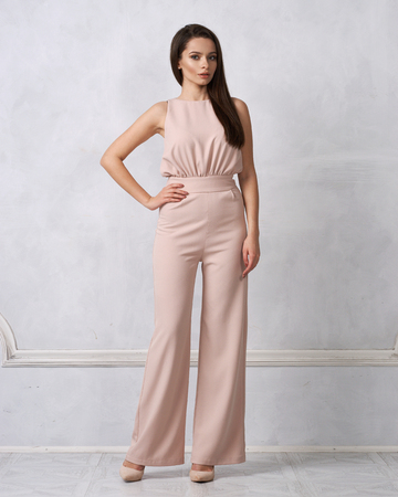 Charming female model with long brunette hair wearing fashionable sleeveless beige jumpsuit and heeled shoes posing against white wall on background. Gorgeous woman dressed in trendy apparel.