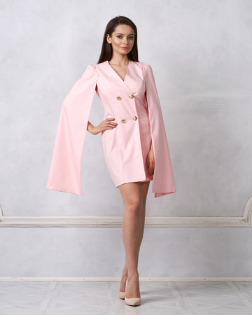 Attractive brunette female model wearing mini pink dress with golden buttons, split, long hanging sleeves and heeled shoes posing against white wall on background. Beautiful woman in trendy outfit. Stock Photo