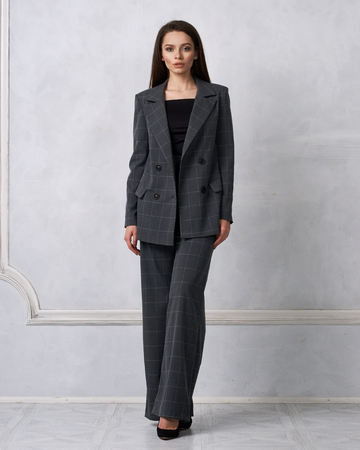 Gorgeous young woman dressed in gray squared jumpsuit, blazer and heeled shoes posing in studio. Beautiful brunette girl demonstrating stylish smart clothing against white wall on background.