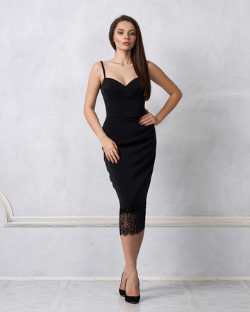Beautiful female model with long brunette hair demonstrating black bodycon dress with straps and lace hem. Young attractive fashionable woman posing in studio against white wall on background.