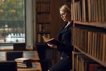 Superbe femme blonde portant un costume en tweed noir et des lunettes debout à côté de la bibliothèque et du livre de lecture. Jeune mannequin séduisante habillée en jupe et veste à la bibliothèque.