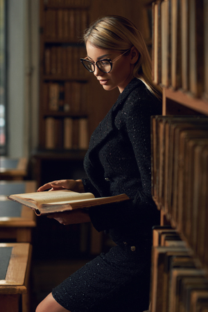Gorgeous blonde woman wearing black tweed suit and glasses standing beside bookcase and reading book. Young seductive female model dressed in skirt and jacket at library.