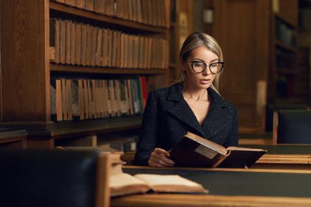 Belle femme blonde vêtue d'une élégante veste en tweed noir et lunettes assis au bureau à côté de la bibliothèque et livre de lecture. Jeune étudiante magnifique étudiant à la bibliothèque.