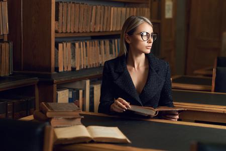 Belle femme blonde portant une élégante veste en tweed noir et des lunettes assis au bureau à côté de la bibliothèque et livre de lecture Jeune étudiante magnifique étudiant à la bibliothèque.