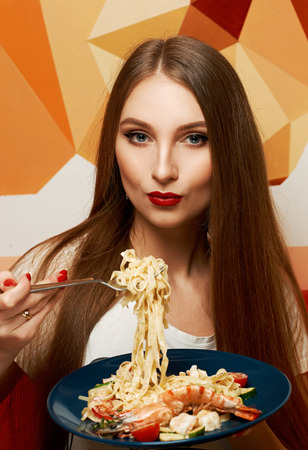 Portrait of attractive long haired woman with slightly ajar mouth and red lips eating Italian pasta with seafood and vegetables. Gorgeous young female model posing with delicious fettuccine on fork.