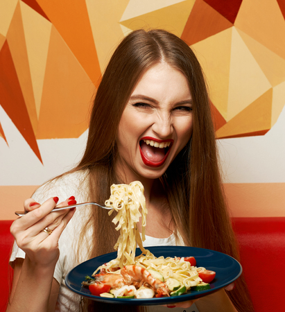 Laughing beautiful long haired woman with expressively opened mouth eating Italian pasta with shrimps and vegetables. Joyful funny young female model posing with appetizing fettuccine on fork.