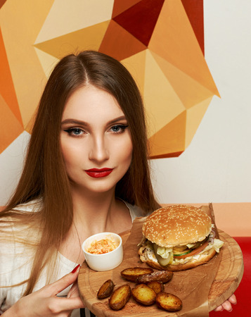 Portrait of beautiful young woman holding round tray with delicious burger, salad and fried potato lying on piece of kraft paper. Elegant female model demonstrating cheeseburger on wooden plate.