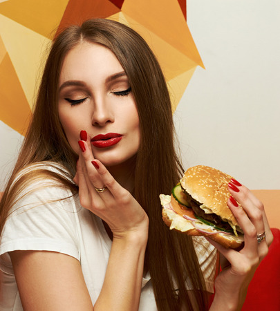 Portrait of playful beautiful sexy woman with red lips holding delicious hamburger and looking at it. Flirty female model posing with tasty burger. Attractive girl with appetizing fast food meal.