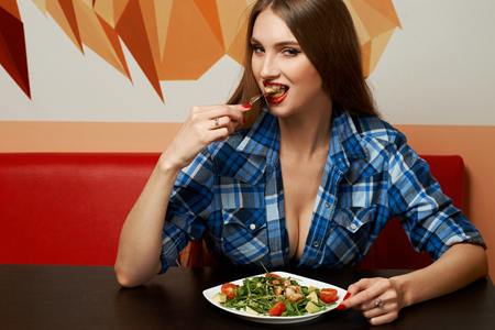 Gorgeous seductive woman dressed in sexy blue unbuttoned checkered shirt eating fresh tasty salad with seafood and vegetables. Pretty long haired female model sitting at restaurant table and posing.