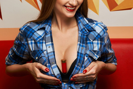 Red shotgun shell, shotshell or cartridge clamped between breasts of young seductive female model dressed in blue checkered unbuttoned knotted shirt and black bra. Concept of dangerous beauty. Standard-Bild