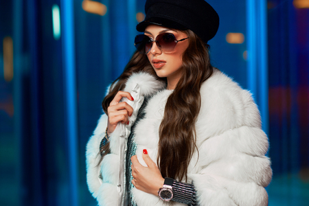 Waist up portrait of stylish young woman wearing large round sunglasses, cap, luxurious white fur coat, standing and posing against glass windows illuminated by pink neon light on background. Stock Photo