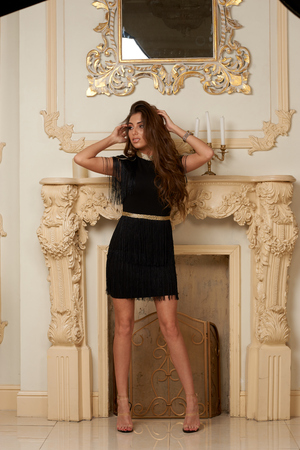 Beautiful stylish slim tall tanned young woman in short black dress and cap posing in luxury interior Stock Photo