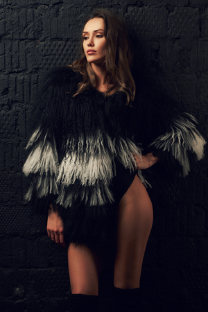 Full body portrait of gorgeous brunette woman wearing fashionable faux fur coat with long black and white hair and over knee boots. Seductive female model posing against gray brick wall on background.