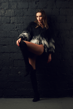 Magnificent caucasian brunette woman wearing trendy faux fur coat with long black and white hair and thigh high boots. Attractive sexy female model dressed in stylish clothing posing with bent leg. Imagens