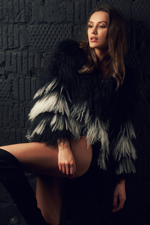 Magnificent caucasian brunette woman wearing trendy faux fur coat with long black and white hair and thigh high boots. Attractive sexy female model dressed in stylish clothing posing with bent leg. Stock Photo