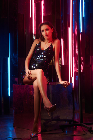 Brunette woman wearing elegant black sequin strap cami dress sitting on large cube with crossed legs. Attractive caucasian female model posing against glowing neon lamps and mirrors on background