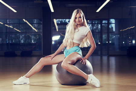 Pretty slim blonde woman with long hair, dressed in white crop top, blue shorts and trainers, sitting on silver exercise ball spreading legs wide apart against two bright lights and gym on background. Stock Photo