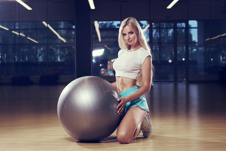 Attractive blonde caucasian woman with long hair, dressed in fitness clothing, kneeling down on wooden floor, holding silver balance ball with hands and posing against large windows on background.
