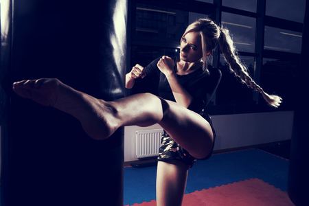 Gorgeous female fighter with blonde hair pulled back in long braid, dressed in black crop top and camouflage shorts, hitting punching bag with her leg. Attractive young woman training in sports club. Stock Photo