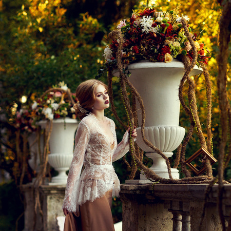 Elegant female model wearing maxi dress and white lace jacket with long sleeves posing on summer terrace beside classical stone balustrade and large flower vases against green foliage on background. Archivio Fotografico
