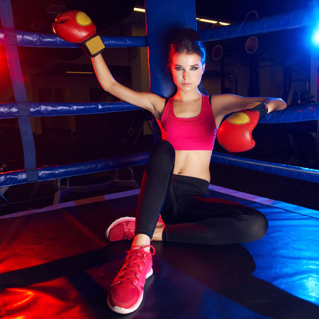 Full body portrait of boxer woman with long dark hair pulled back in pony tail, wearing pink sports bra, leggings, trainers and red boxing gloves, sitting in corner of ring and leaning on ropes. Stock Photo