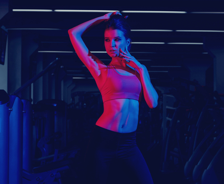 Waist up portrait of young attractive brunette woman dressed in sports clothes illuminated by faint pink light. Gorgeous confident slim female fitness model wearing top and leggings posing at gym.