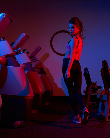 Gorgeous slim woman with long brunette hair tied up in pony tail, dressed in sports clothing, walking between rows of exercise machines, back view. Beautiful female fitness model posing at gym.