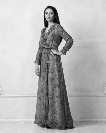 Full body portrait of attractive young woman posing in elegant maxi chiffon evening dress with motley pattern, long sleeves and frills. Brunette girl standing against white wall on background.