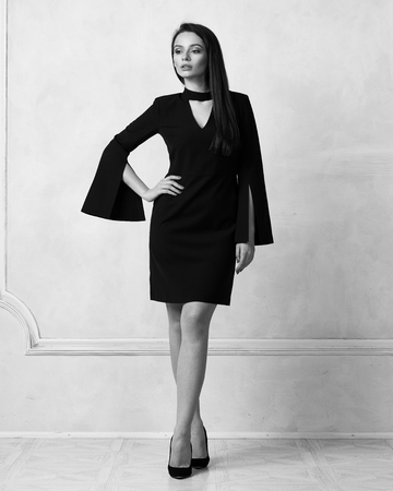 Pretty female model wearing black mini blazer dress with four buttons and heeled shoes posing in studio. Beautiful woman in trendy outfit standing with crossed legs against white wall on background.