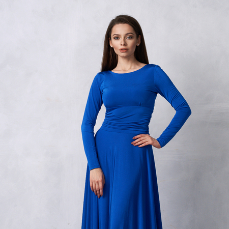 Young woman with long brunette hair dressed in elegant evening blue maxi dress with long sleeves posing in studio. Gorgeous female model standing against white wall decorated with classic moldings. 스톡 콘텐츠