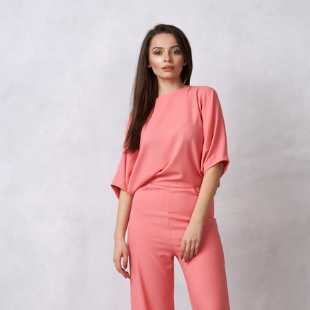 Young brunette woman with long straight hair wearing trendy short sleeved pink jumpsuit and nude heeled shoes posing against white wall on background. Female model demonstrating fashionable outfit.